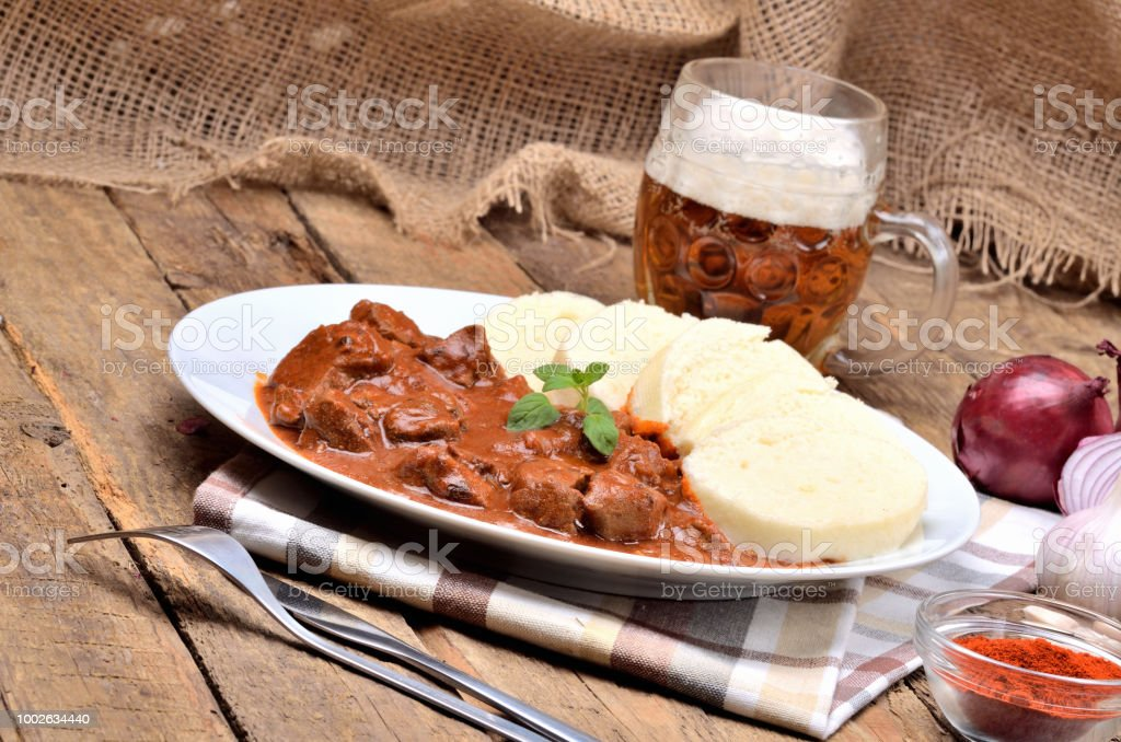 Pork goulash meat with dumplings on white plate, cutlery, cold beer, garlic, onion, pepper, tablecloth in the background - typical Czech food stock photo