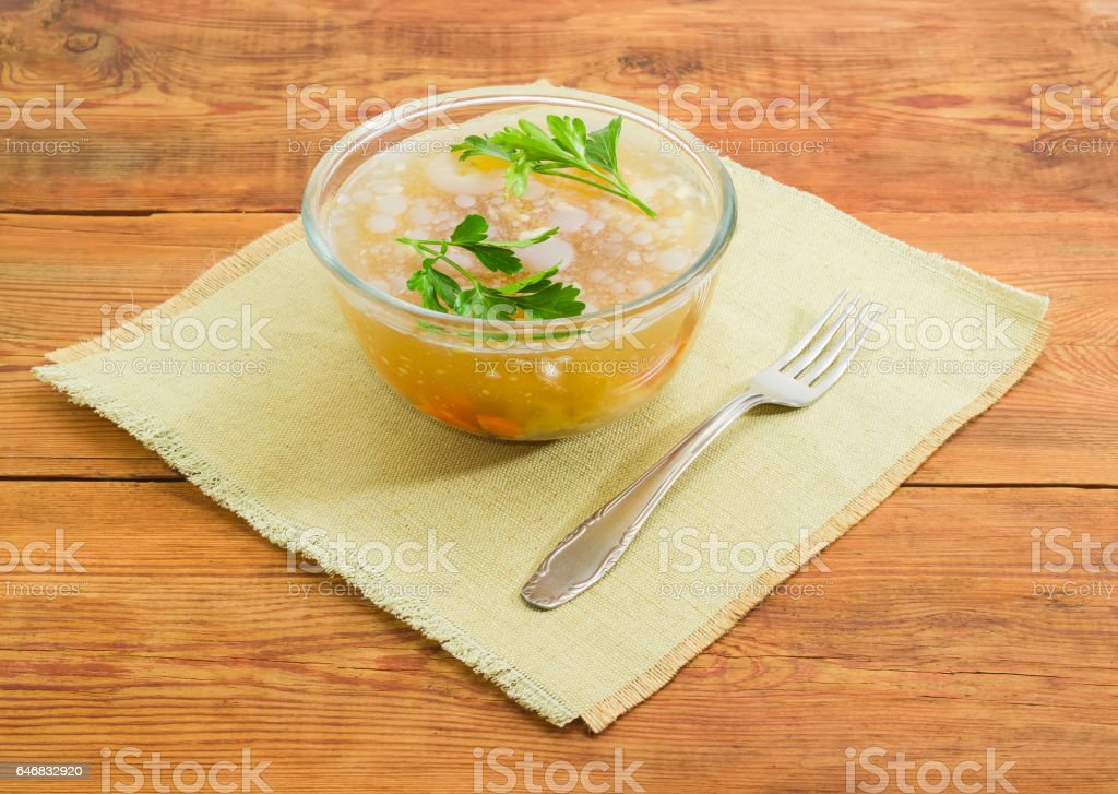 Pork jelly in glass bowl and fork on wooden surface stock photo