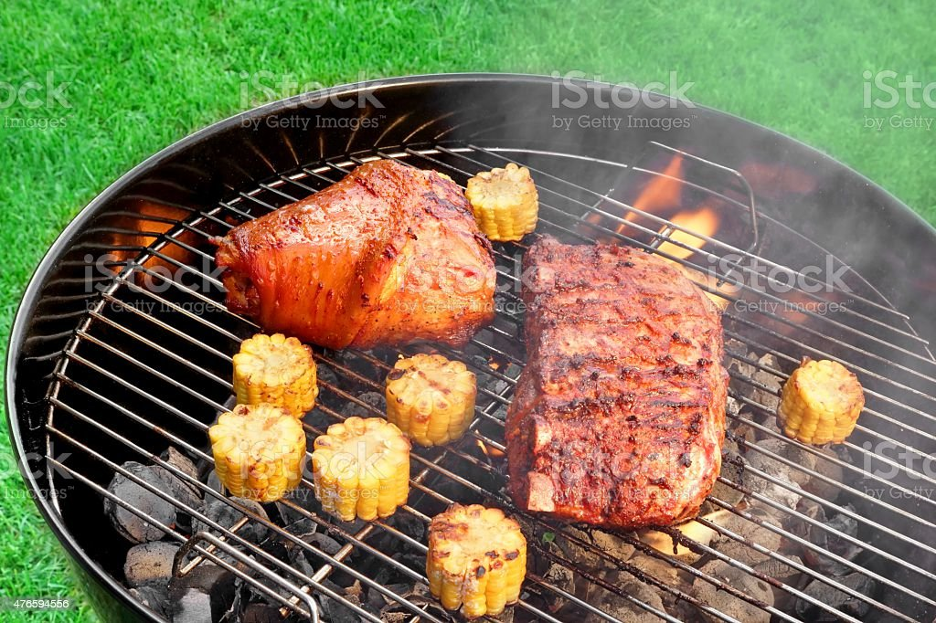 BBQ Pork Knuckle And Spareribs on The Flaming Charcoal Grill stock photo