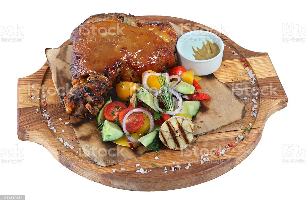 Pork knuckle with vegetable salad on round wooden board, isolated. stock photo