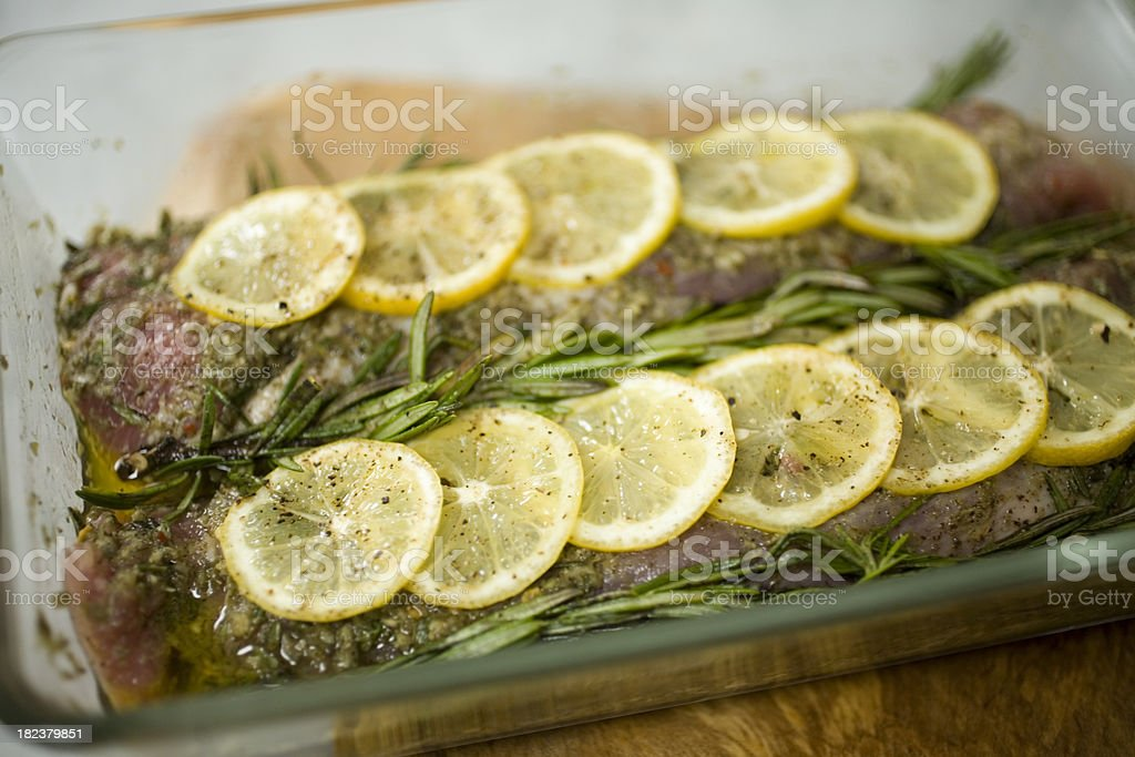 Pork loin marinating with lemons and herbs stock photo