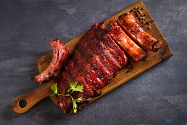 Pork loin ribs served on chopping board Pork loin ribs served on chopping board. View from above, top pork stock pictures, royalty-free photos & images
