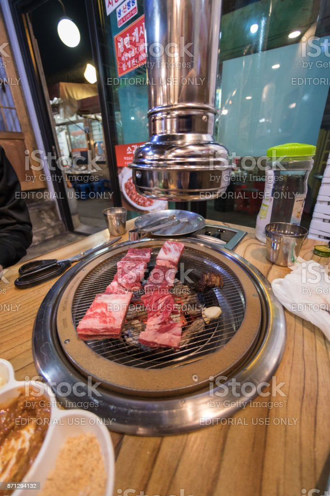 Pork meat cooking on a Korean BBQ - street food in Seoul stock photo