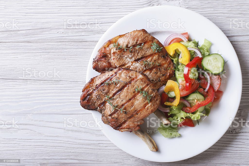 Pork meat grilled with fresh vegetable salad top view stock photo