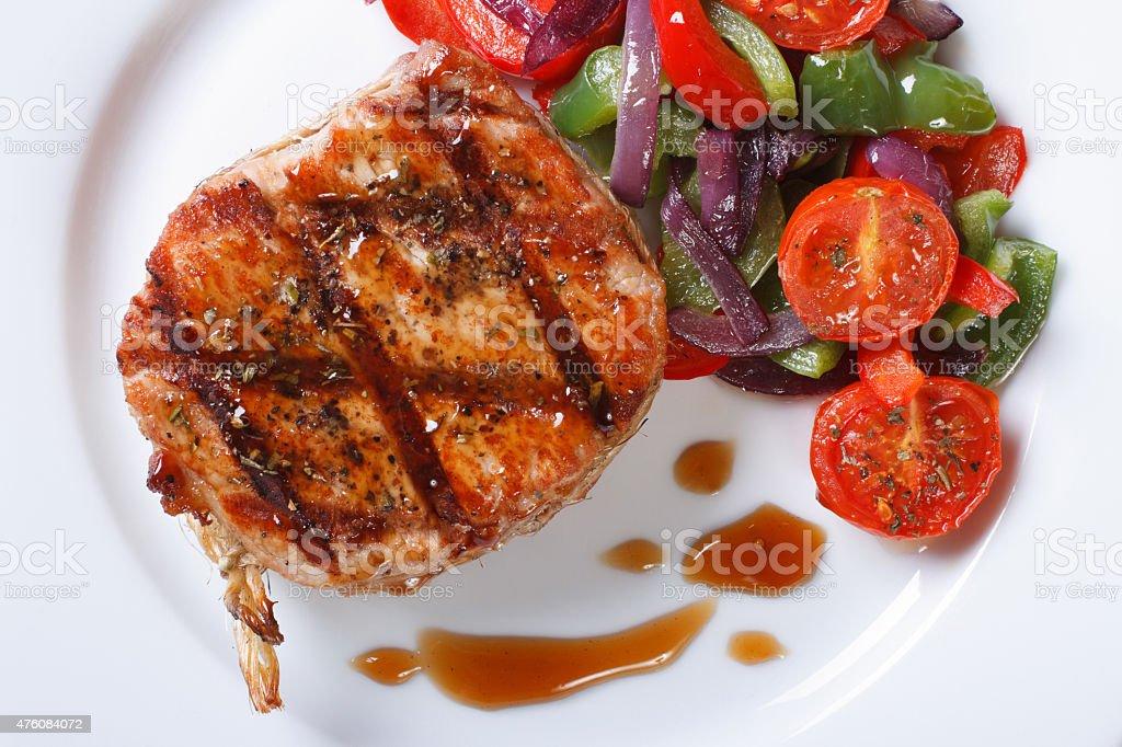 Pork medallions with vegetables top view horizontal macro stock photo