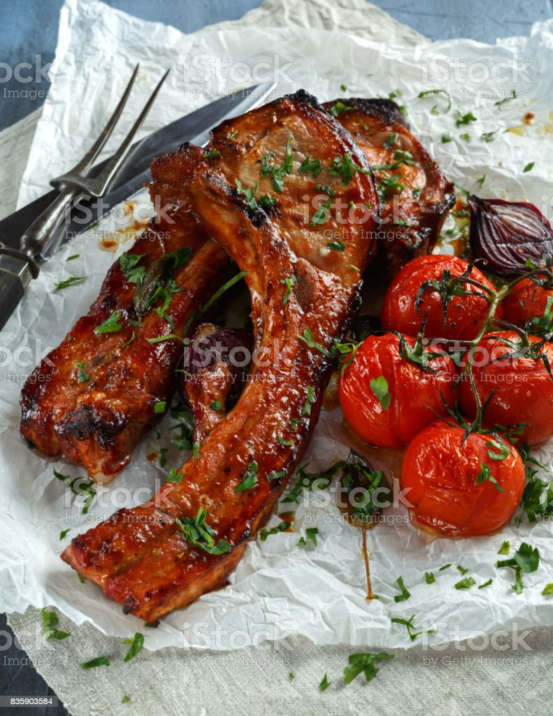 Pork middle chop roast with sweet and sour souce, baked tomatoes and red onion stock photo