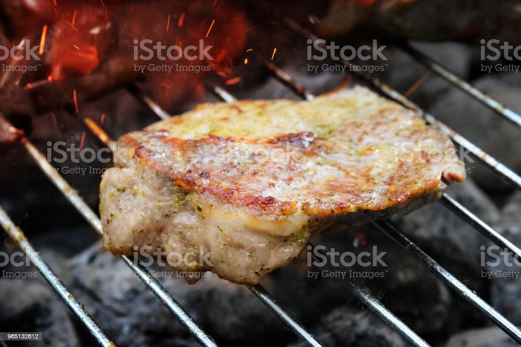 Pork neck steak on the barbecue grill with glowing charcoal briquettes and sparks zbiór zdjęć royalty-free
