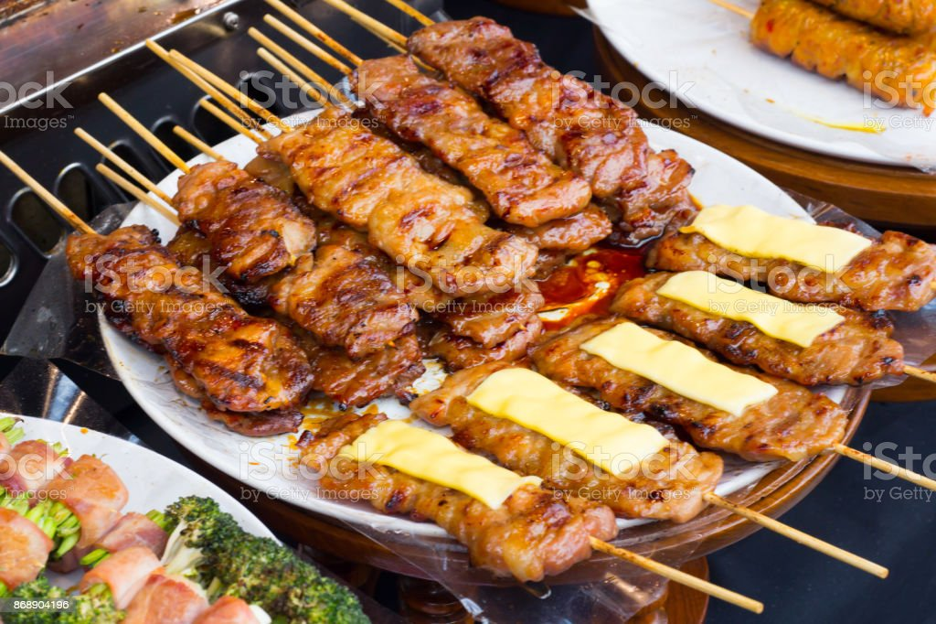 pork on the grill with flame. / Street food in Thailand. / thai style bbq grilled pork./ Grilled pork skewers at night market. stock photo
