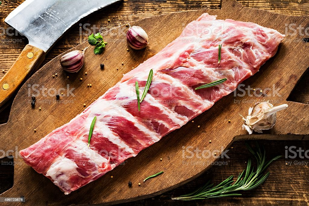 Pork ribs and meat cleaver on wooden cutting board stock photo
