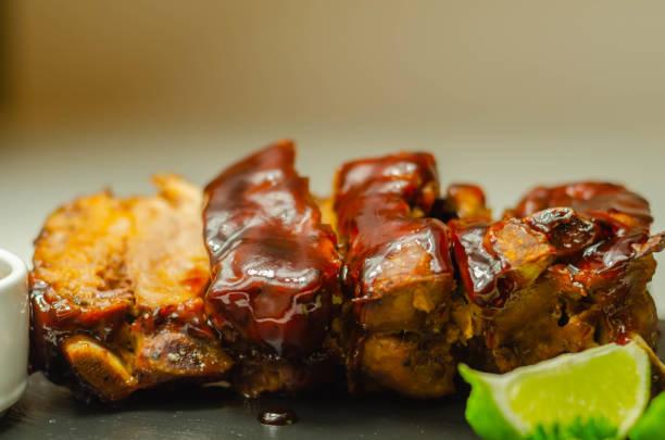 Costelas de porco em um tempero de churrasco com sabor esfumaçado com um molho de churrasco de mel, - foto de acervo