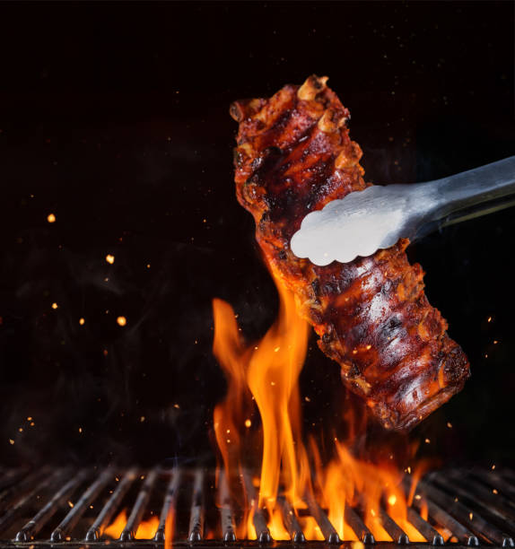 pork ribs over flaming grill grid, isolated on black background. - ribs stock photos and pictures