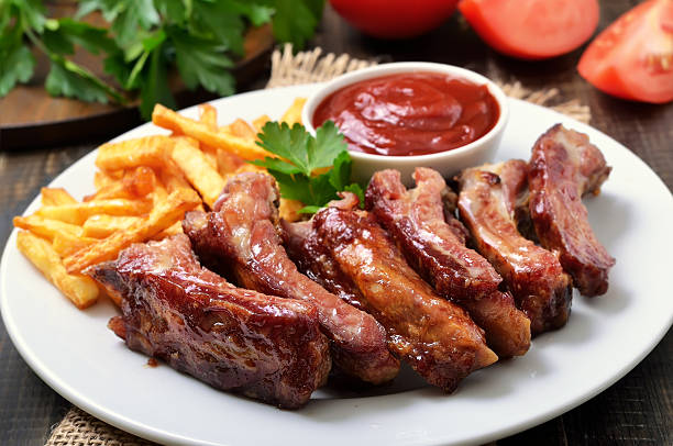 pork ribs, potato fries and tomato sauce, close up view - ribs stock photos and pictures
