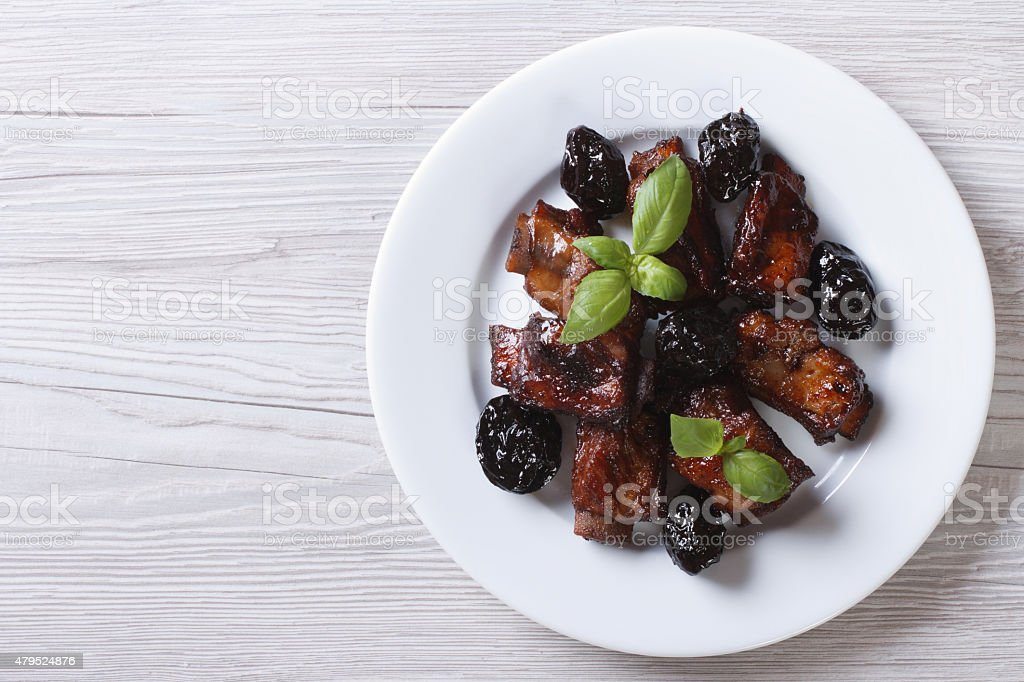 Pork ribs stewed with prunes on plate. horizontal top view stock photo