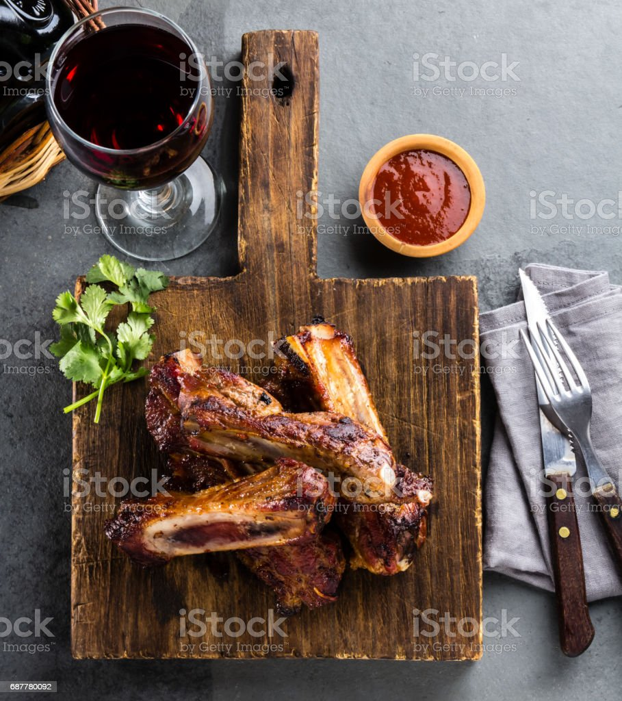 Pork ribs with chili sauce on wooden board and red wine on gray slate background stock photo