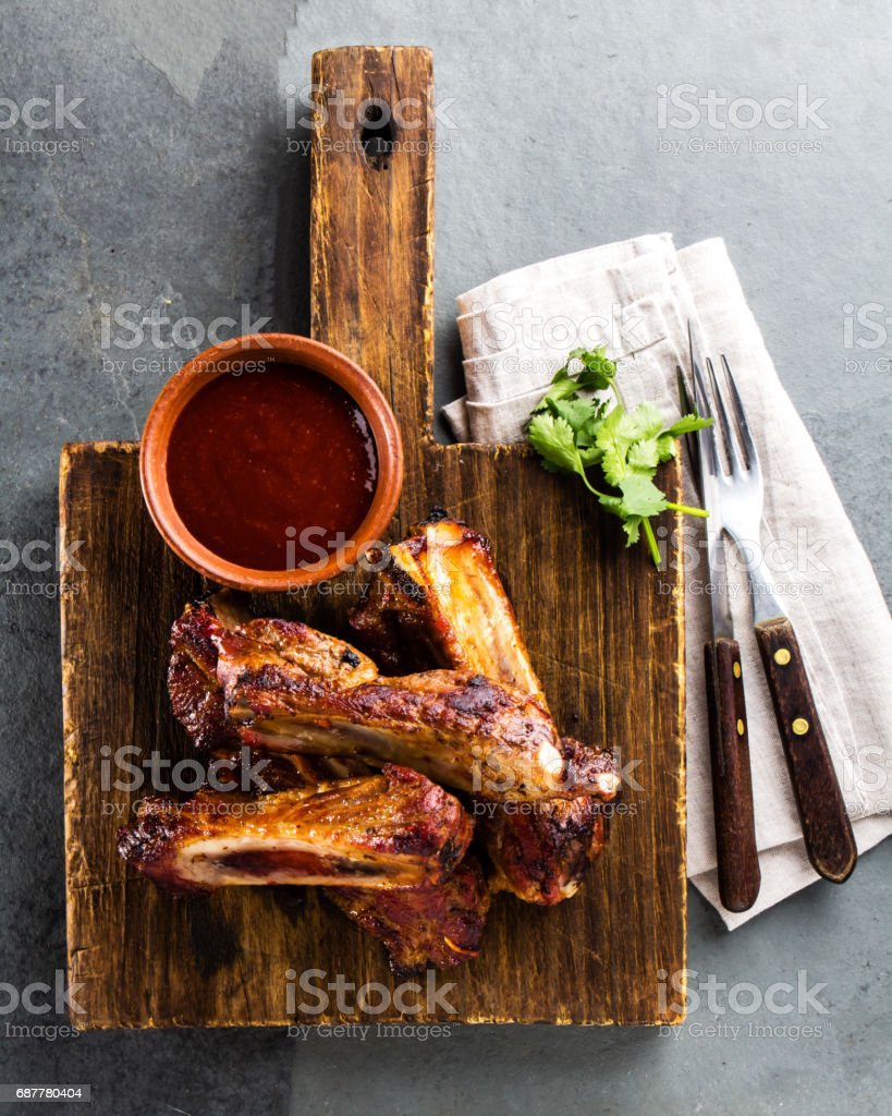 Pork ribs with chili sauce on wooden cutting board. Slate background stock photo