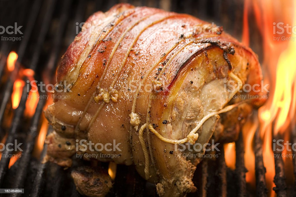 A pork roast on a grill with flames stock photo