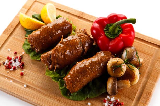 schweinefleisch-rouladen und gemüse auf weißem hintergrund - paprikaschnitzel stock-fotos und bilder