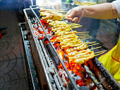 Pork satay being grilled over charcoal fire at night market in Bangkok. Street food.