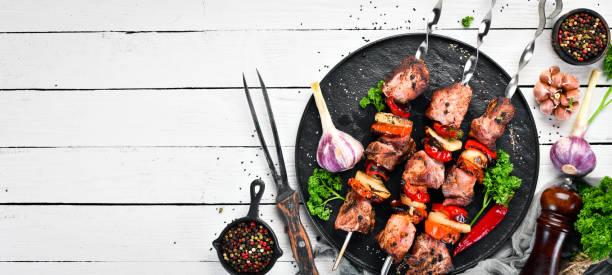 Kebab do shish da carne de porco com cebolas e tomates. Churrasco. Vista superior. Espaço livre para o seu texto. Estilo rústico. - foto de acervo