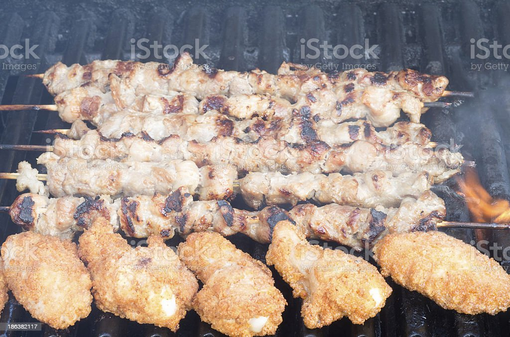 Pork skewers and chicken wings on grill royalty-free stock photo