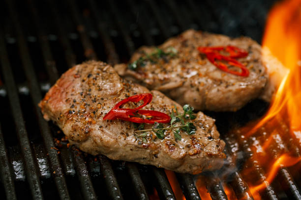 pork steak on bbq grill with flame stock photo