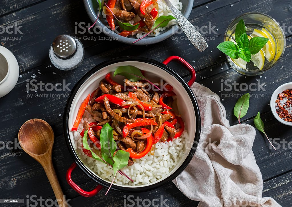 Pork stir fry with red peppers and rice in pot stock photo