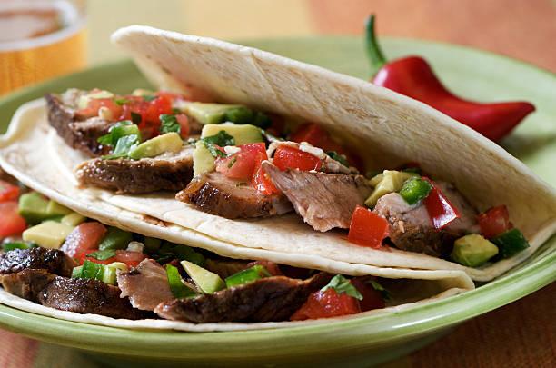 tacos mit schweinefleisch - kräuterfaltenbrot stock-fotos und bilder