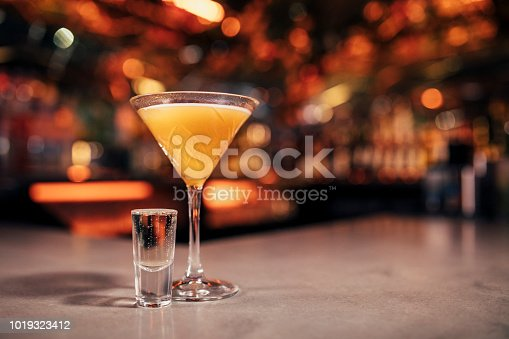 Front view of a Pornstar Martini cocktail with a shot of Prosecco  on a bar counter. The background of the image is defocused lights and the back of the bar. This cocktail has passionfruit as a garnish on the cold drink.