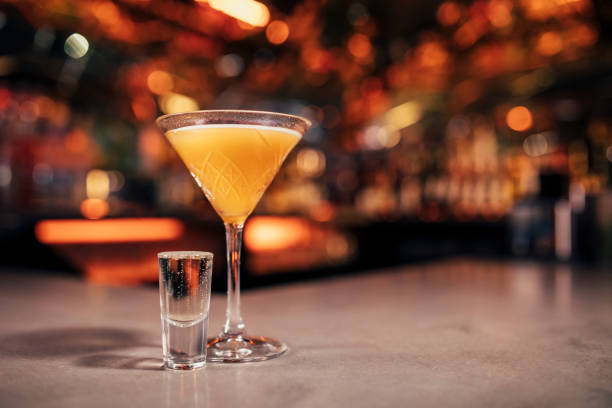 Pornstar Martini Cocktail Front view of a Pornstar Martini cocktail with a shot of Prosecco  on a bar counter. The background of the image is defocused lights and the back of the bar. This cocktail has passionfruit as a garnish on the cold drink. martini stock pictures, royalty-free photos & images