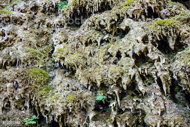 Porous melted flowstone stalagmites on a dry waterfall covered in moss