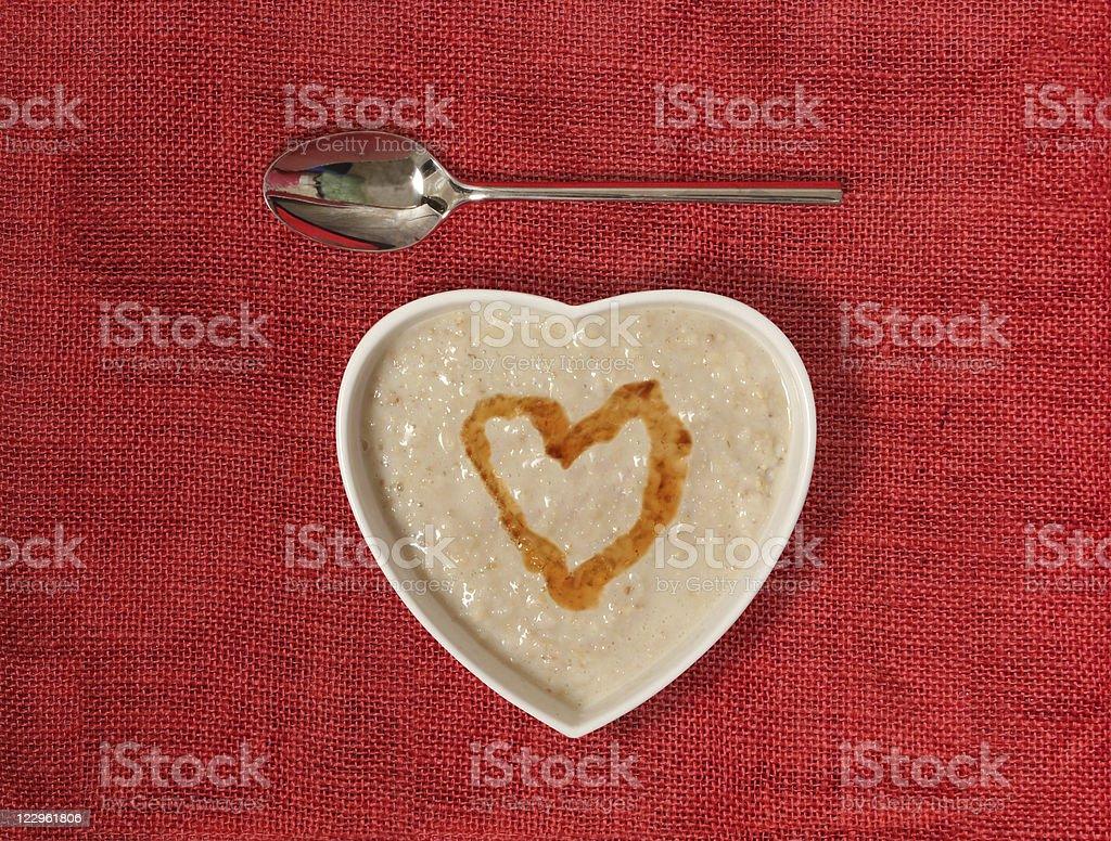 Gachas de avena en un tazón con la miel en forma de corazón - foto de stock