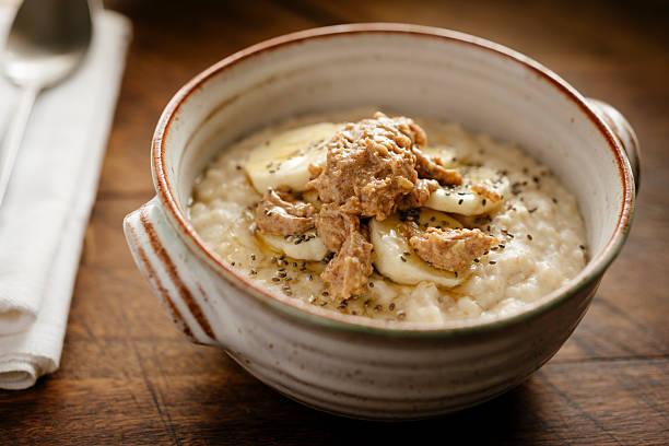 Porridge topped with slice banana, chia seeds, honey, peanut butter