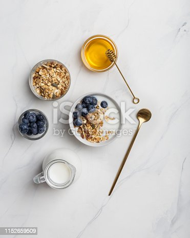 Porridge with nuts, yogurt, blueberries, honey with honey stick, with golden tableware on white marble background. Copy space for text, flat lay