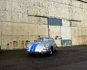 Bicester Oxfordshire, UK - January 8 2017: Porsche 356 in front of Bicester Airfield hanger doors. The 356 was Porsche's first sports car, being lightweight and nimble-handling, rear-engine, rear-wheel drive. This attractive coupe version is silver with very racy blue stripes.