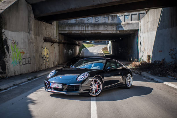 Porsche 911 Carrera 4 Porsche 911 Carrera 4, model for 2018 with aluminium wheels. Black matt color dominate on the car and have very sport look. This car is one of the most popular sport car in the world. Design that Porsche 911 have is really unique. This was shoot outside in a daily drive. porsche stock pictures, royalty-free photos & images