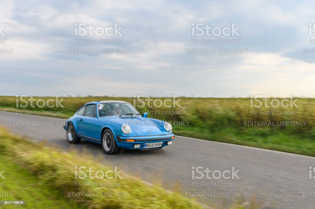 Porsche 911 classic sports car driving on a country road stock photo