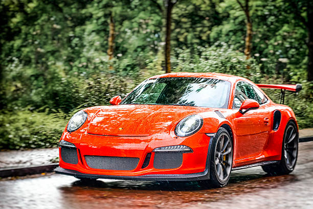 Porsche 911 GT3 RS sports car Zwolle, The Netherlands - September 5, 2015: Orange Porsche 911 GT3 RS sports car driving on the street in the city of Zwolle in the rain. porsche stock pictures, royalty-free photos & images