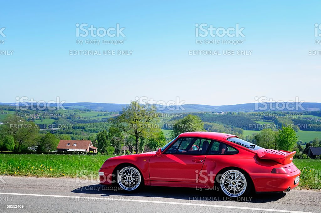 Porsche 911 Turbo sports car in a landscape with hills stock photo