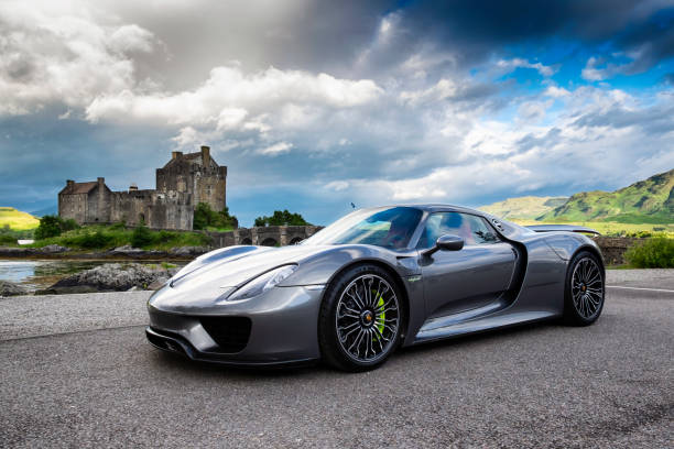 Porsche 918 At Eilean Donan Castle In Scotland Eilean Donan, Scotland - August 3, 2015: The spectacular Porsche 918 Spyder, a mid-engined plug-in hybrid sports car, parked near the unmistakable shape of Eilean Donan Castle in the Western Highland of Scotland. porsche stock pictures, royalty-free photos & images