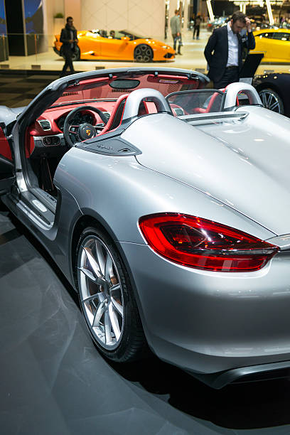 Porsche Boxster Spyder open sports car Brussels, Belgium - Januari 12, 2016: Silver Porsche Boxster Spyder open sports car rear view at the Porsche stand. The Porsche Boxster Spyder is the lightweight version of the Porsche Boxster. The car is on display during the 2016 Brussels Motor Show. The car is displayed on a motor show stand, with lights reflecting off of the body. There are people looking around and other cars on display in the background. porsche stock pictures, royalty-free photos & images