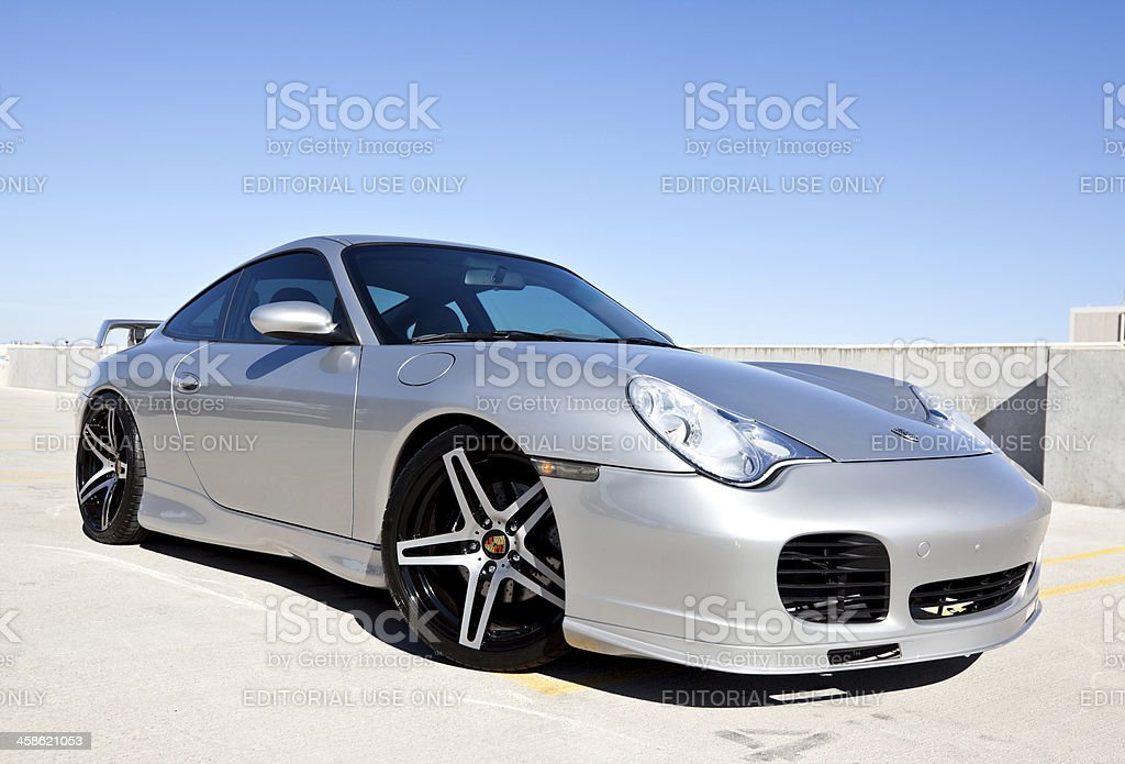 Porsche Carerra 2002 Scottsdale, United States - November 17, 2011: A photo of a parked silver 2002 Porsche Carerra. The Carerra from Porsche is known for its independent rear suspension and rear engine. Car Stock Photo
