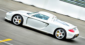 Assen, The Netherlands - May 19, 2013: Silver Porsche Carrera GT supercar driving around the race track during the 2013 Viva Italia event at the TT race track at Assen, The Netherlands.