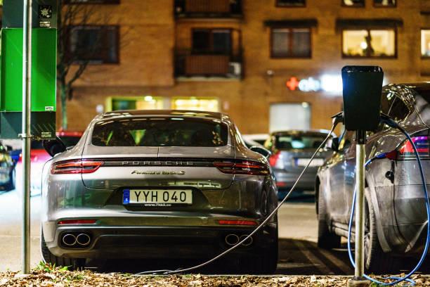 porsche panamera s electic fordon och tesla elfordon parkerade på heden för charing cross - elbilar laddning sverige bildbanksfoton och bilder