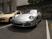 Angers, France - June 8th 2013 : Focus on a silver colored Porsche Carrera 4S parked in the street.