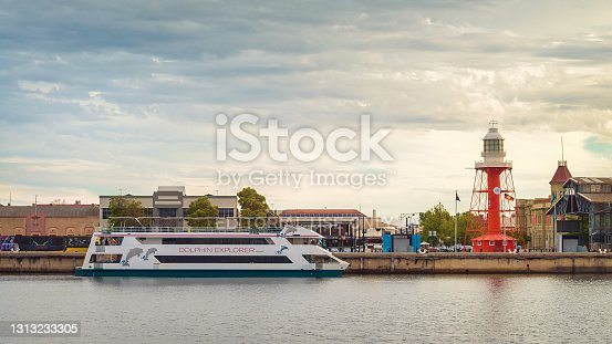 Port Adelaide, Australia - December 8, 2018: Iconic Port Adelaide lighthouse with Dolphin Explorer boat viewed across Port River at sunset
