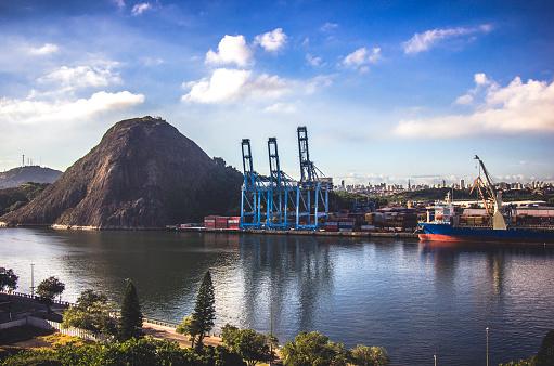 Porto comercial da cidade de Vitória no Brasil. Paisagem que mescla a natureza e a artificialidades das gruas de transporte de carga.