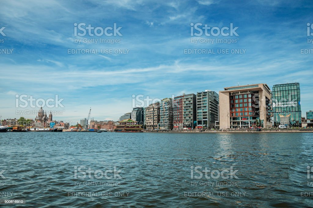 Port, church towers and modern buildings on canal bank and blue sky in Amsterdam. stock photo
