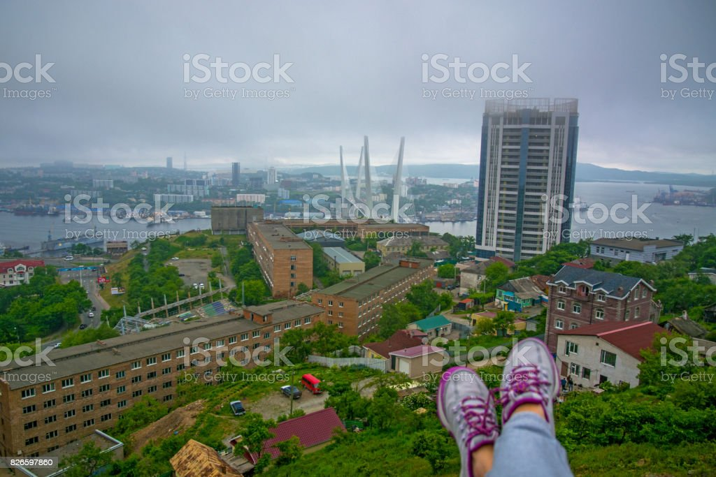 port city view from the heights, high Bay braced bridge, thick fog. Marine City, bottom visible female legs. stock photo