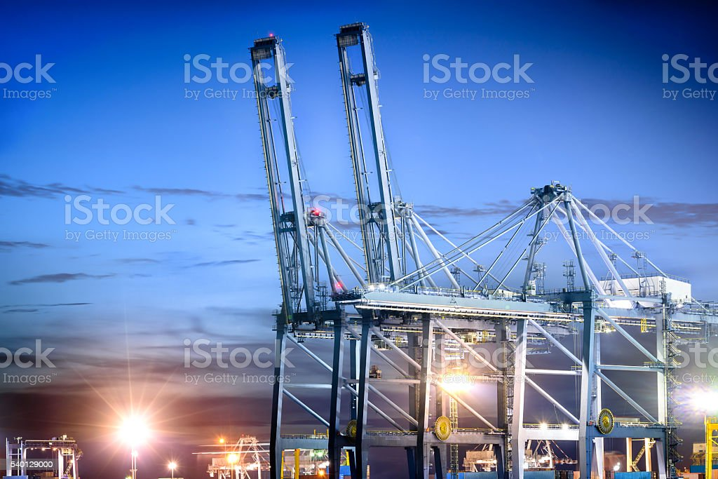 Port cranes working in shipyard at dusk stock photo