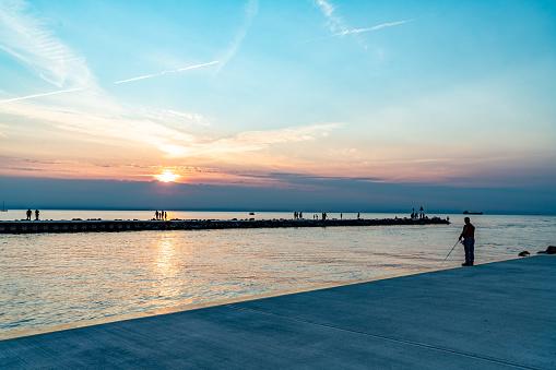 A man is fishing at Lake Ontario at dusk, St. Catharines, Ontario, Canada.